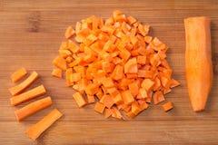 Χωρισμένα σε τετράγωνα ακατέργαστα καρότα σε έναν τεμαχίζοντας πίνακα Στοκ Εικόνες