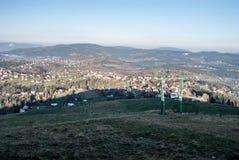 Χωριό Koniakow με τους λόφους γύρω από το λόφο Ochodzita στα βουνά Beskid Slaski στην Πολωνία Στοκ Εικόνες