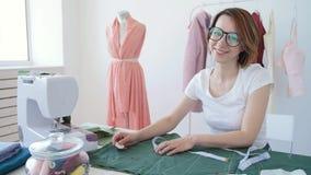 Χόμπι και μικρή επιχείρηση Νέος θηλυκός ράφτης που εργάζεται με το ύφασμα υφασμάτων στο εργαστήριο απόθεμα βίντεο
