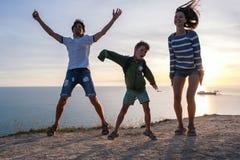 Χόμπι οικογενειακής διασκέδασης σε ένα βουνό με την άποψη παραλιών Μπαμπάς, mom, και χορός γιων στο ηλιοβασίλεμα Μπροστινή όψη Στοκ εικόνα με δικαίωμα ελεύθερης χρήσης