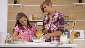 Χύνοντας αυγά κοριτσιών στο αλεύρι απόθεμα βίντεο