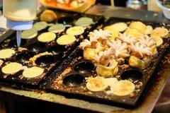 Χύνοντας αλεύρι στη μαύρη σόμπα για & x22 Μωρό Octopus& x22  στις ιαπωνικές σφαίρες Takoyaki Στοκ εικόνα με δικαίωμα ελεύθερης χρήσης