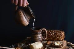 Χύνοντας γάλα από μια κανάτα στο φλυτζάνι στα χέρια, βουτύρου, σκοτεινό ψωμί δημητριακών με τους σπόρους ηλίανθων που λερώνονται, στοκ εικόνες