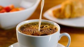 Χύνοντας γάλα σε ένα φλιτζάνι του καφέ απόθεμα βίντεο