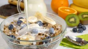 Χύνοντας γάλα στις νιφάδες και τα φρούτα δημητριακών για το πρόγευμα σε σε αργή κίνηση απόθεμα βίντεο
