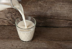 Χύνοντας γάλα από μια καράφα στο γυαλί στοκ εικόνες