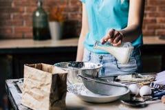 Χύνοντας γάλα γυναικών στο κύπελλο στοκ φωτογραφία