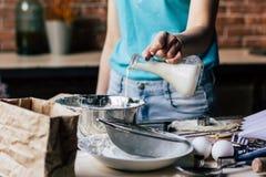 Χύνοντας γάλα γυναικών στο κύπελλο στοκ εικόνες