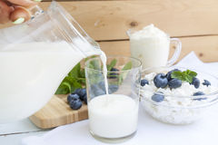 Χύνοντας γάλα στο γυαλί στον πίνακα Στοκ Φωτογραφία