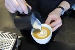 Χύνοντας γάλα Barista στο φλυτζάνι καφέ προετοιμάζοντας το φρέσκο καφέ Στοκ Φωτογραφίες