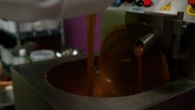 Χύνοντας λειώνοντας σοκολάτα εργαζομένων στη μηχανή συνδυασμού φιλμ μικρού μήκους