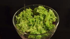 Χύνοντας ελαιόλαδο στη σαλάτα φρέσκων λαχανικών στο κύπελλο απόθεμα βίντεο
