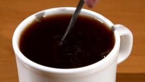 Χύνοντας ζάχαρη κουταλιών σε ένα φλιτζάνι του καφέ, ξύλο απόθεμα βίντεο
