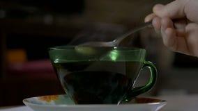 Χύνοντας ζάχαρη σε ένα φλυτζάνι του καυτού καφέ το πρωί απόθεμα βίντεο