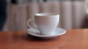 Χύνοντας ζάχαρη στο άσπρο φλυτζάνι καφέ στο ξύλινο υπόβαθρο απόθεμα βίντεο