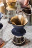 Χύνοντας ζεστό νερό δοχείων εκμετάλλευσης χεριών στο στάζοντας καφέ εκλεκτικός Στοκ εικόνα με δικαίωμα ελεύθερης χρήσης