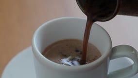 Χύνοντας καφές στο φλυτζάνι καφέ από το δοχείο καφέ φιλμ μικρού μήκους