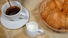 Χύνοντας καφές στο φλυτζάνι με Croissant απόθεμα βίντεο