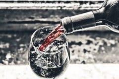 Χύνοντας κρασί κόκκινο κρασί σε ένα γυαλί Στοκ Εικόνες