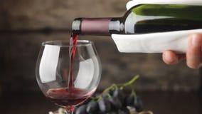 Χύνοντας κρασί wineglass στο ξύλινο υπόβαθρο απόθεμα βίντεο