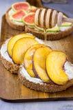 Χύνοντας μέλι με ξύλινο dipper στη φρυγανιά με ολόκληρη τη φέτα ψωμιού σίκαλης πίτουρου σιταριού με το τυρί κρέμας, ροδάκινα, σύκ Στοκ φωτογραφία με δικαίωμα ελεύθερης χρήσης