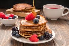 Χύνοντας μέλι στις τηγανίτες με τα βακκίνια και τις φράουλες και το φλυτζάνι του κόκκινου χυμού στοκ φωτογραφία