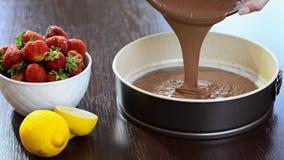 Χύνοντας μίγμα κέικ σοκολάτας στον κασσίτερο Κατασκευή της ζύμης ζύμης φιλμ μικρού μήκους