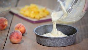 Χύνοντας μίγμα κέικ στον κασσίτερο Κατασκευή της ζύμης ζύμης Κατασκευή του κέικ ροδάκινων απόθεμα βίντεο