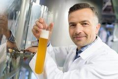Χύνοντας μπύρα ζυθοποιών στον κύλινδρο πυκνόμετρων στο εργοστάσιο ζυθοποιείων στοκ εικόνες