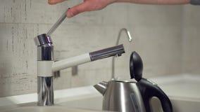 Χύνοντας νερό από τη βρύση σε μια ηλεκτρική κατσαρόλα φιλμ μικρού μήκους
