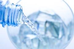 Χύνοντας νερό σε ένα κομψό γυαλί με τις πτώσεις πάγου και νερού Στοκ Εικόνα