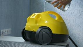 Χύνοντας νερό στην κίτρινη καθαρότερη συσκευή ατμού πρίν χρησιμοποιεί το κινηματογράφηση σε πρώτο πλάνο χεριών φιλμ μικρού μήκους