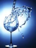 Χύνοντας νερό στο γυαλί με καταβρεγμένος έξω στοκ εικόνα