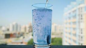 Χύνοντας νερό στο γυαλί με το χάπι σε σε αργή κίνηση Παφλασμός της aspirin, λύση πονοκέφαλου στο θολωμένο υπόβαθρο πόλεων απόθεμα βίντεο