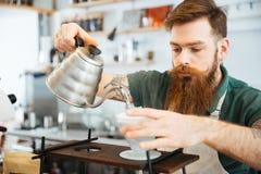 Χύνοντας νερό Barista στο έδαφος καφέ με το φίλτρο στοκ φωτογραφία