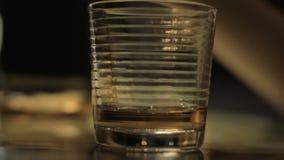 Χύνοντας οινόπνευμα χεριών κινηματογραφήσεων σε πρώτο πλάνο από το μπουκάλι στο γυαλί, πίνοντας και βάζοντας στον πίνακα φιλμ μικρού μήκους