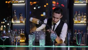 Χύνοντας ποτό μπάρμαν από το μπουκάλι στο ποτηράκι στο φραγμό απόθεμα βίντεο