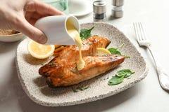 Χύνοντας σάλτσα γυναικών επάνω στο νόστιμο μαγειρευμένο σολομό στοκ εικόνα με δικαίωμα ελεύθερης χρήσης
