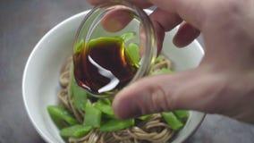 Χύνοντας σάλτσα σόγιας στα νουντλς φαγόπυρου με τα φασόλια απόθεμα βίντεο