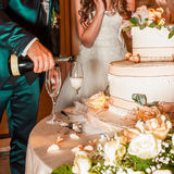 Χύνοντας σαμπάνια γαμπρών στα γυαλιά κοντά σε ένα γαμήλιο κέικ Στοκ φωτογραφία με δικαίωμα ελεύθερης χρήσης