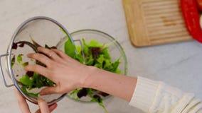 Χύνοντας σαλάτα φρέσκων λαχανικών σε ένα κύπελλο γυαλιού απόθεμα βίντεο