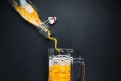 Χύνοντας σειρές από το μπουκάλι στην κούπα γυαλιού μπύρας ενάντια στη μαύρη αφηρημένη minimalistic έννοια υποβάθρου Στοκ Εικόνες