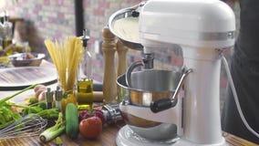 Χύνοντας σκόνη αλευριού αρχιμαγείρων στον αναμίκτη για την προετοιμασία της ζύμης Χύνοντας αλεύρι Baker στη μηχανή κουζινών για τ απόθεμα βίντεο