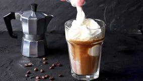 Χύνοντας στο γυαλί με τον καφέ πάγου παγωτού την κτυπημένη σάλτσα κρέμας και σοκολάτας, που εξυπηρετείται με με τα φασόλια καφέ π φιλμ μικρού μήκους