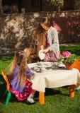 Χύνοντας τσάι κοριτσιών στην αδελφή της στο κόμμα τσαγιού παιχνιδιών Στοκ Εικόνα