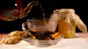 Χύνοντας τσάι με το μέλι, την πιπερόριζα και την κανέλα απόθεμα βίντεο