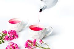 Χύνοντας τσάι προσώπων με τα ροδαλά λουλούδια σε έναν πίνακα Στοκ φωτογραφία με δικαίωμα ελεύθερης χρήσης