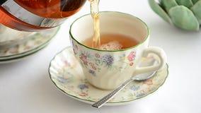 Χύνοντας τσάι στη φλυτζάνα τσαγιού απόθεμα βίντεο