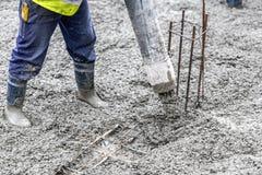 Χύνοντας τσιμέντο και σκυρόδεμα εργαζομένων με το σωλήνα αντλιών Στοκ Εικόνα
