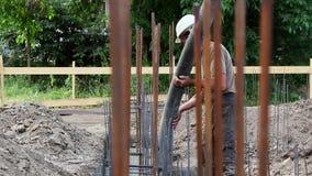 Χύνοντας τσιμέντο και σκυρόδεμα εργατών οικοδομών με το σωλήνα αντλιών φιλμ μικρού μήκους